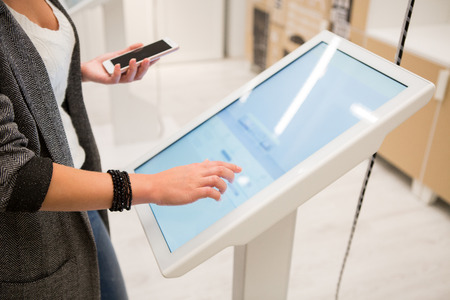 Foto de A woman touching the screen of self service device in the store. - Imagen libre de derechos