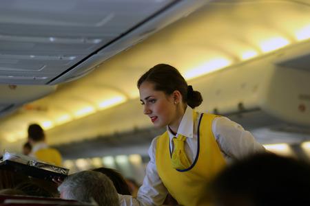 Photo pour Beautiful flight attendant in an airplane smiling. Ukraine - image libre de droit