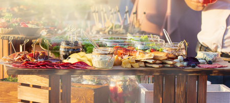 Foto de Beautifully decorated catering banquet table with different food snacks and appetizers with sandwich, on corporate christmas birthday kids party event or wedding celebration - Imagen libre de derechos