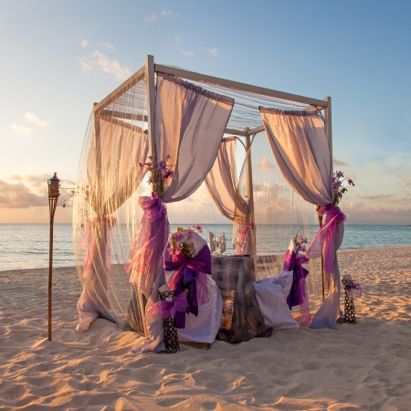 Foto de Beautiful Decorated Romantic Wedding Table on Sandy Tropical Caribbean Beach at Sunset - Imagen libre de derechos
