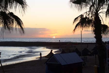 Foto de Sunset at beach and Atlantic Ocean panorama in holiday resort Playa de las Americas on Canary Island Tenerife, Spain - Imagen libre de derechos