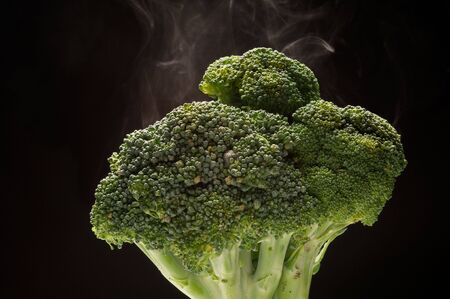 Close up on broccoli with  steam on black background