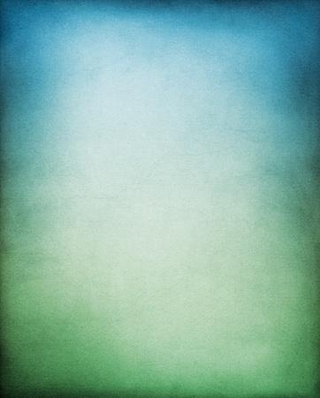 Photo pour A textured paper backgrouund with a green to blue gradation. - image libre de droit