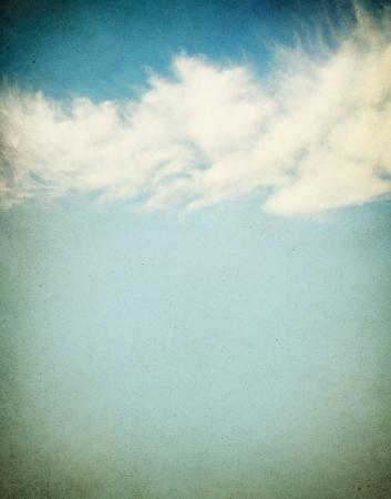 Foto de Ethereal and puffy clouds on a grunge paper background.  Image has a distinct paper grain and texture. - Imagen libre de derechos
