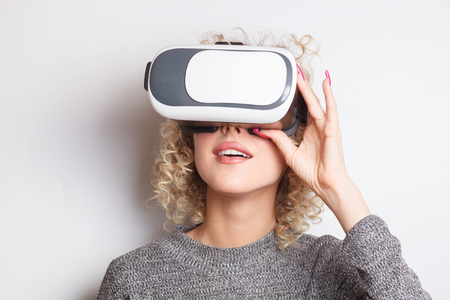 Photo pour wondering blonde young caucasian woman with virtual reality glasses - image libre de droit