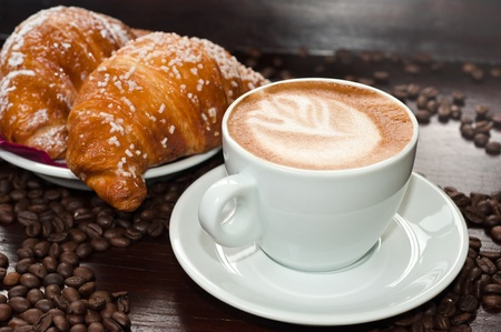 Cappuccino and croissant with coffee beans
