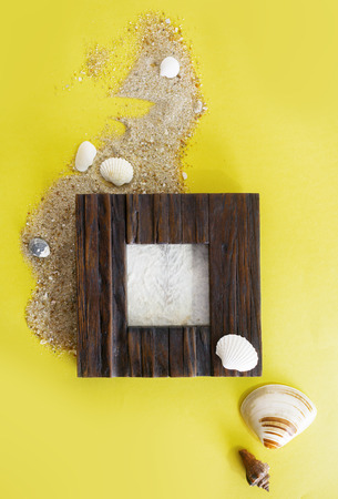 Photo for Empty photo frame with sea shells on sand over yellow paper. Travel, beach vacation concept. Text space. - Royalty Free Image