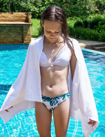 Photo pour Young cute teen girl in bikini and white towel comes out of the pool. Vacation, summer activity, travel concept - image libre de droit
