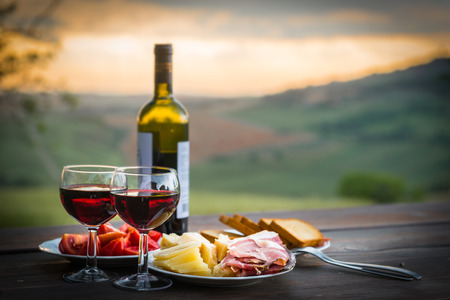 Foto de still life Red wine  ,cheese and prosciutto. Romantic dinner  outdoors - Imagen libre de derechos