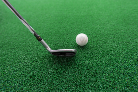 Photo pour Golf club and ball on a synthetic grass mat at a practice range. - image libre de droit