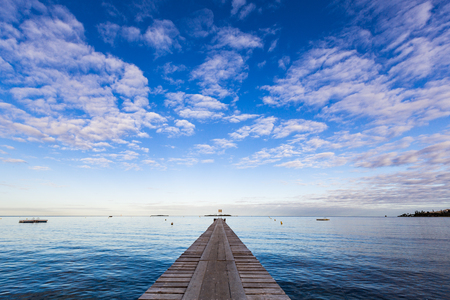Photo pour A symmetrical early morning landscape photo with a low horizon, looking along a wooden pier to the calm blue waters of Anse Vata Bay, Noumea, New Caledonia. - image libre de droit