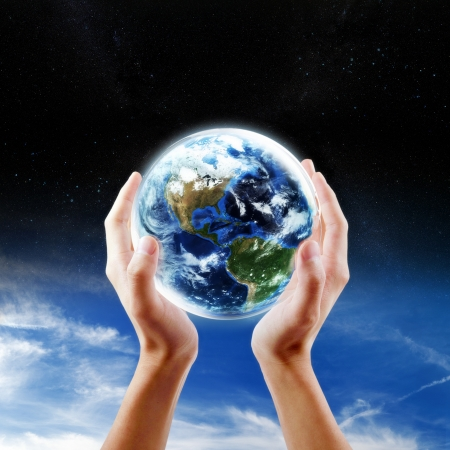 Saving Earth concept, Hands holding Earth with sky and space background