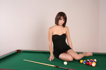 Sexy hot brunette woman sitting on a pool table