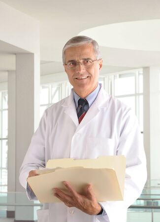 Middle aged male doctor in lab coat holding a manila folder in modern medical office setting.