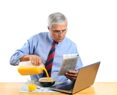Middle aged man pouring Orange Juice into his breakfast cereal bowl insead of milk . He is in front of his laptop computer reading the morning newspaper. Horizontal format isolated over white.