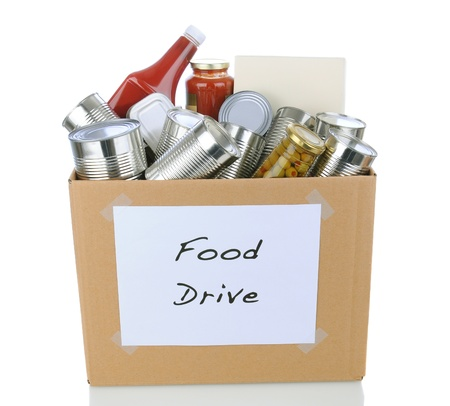 A box full of canned and packaged foodstuff for a charity food donation drive. Isolated on white with reflection.