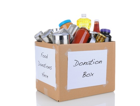 A box full of canned and packaged foodstuff for a charity food donation drive  Isolated on white with reflection
