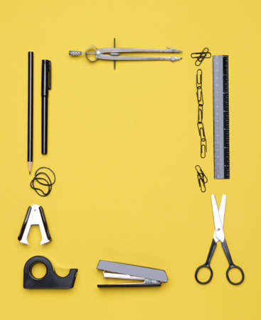 Office and back to school supplies on a yellow background Looking down on the all black and chrome tools from an overhead angle The items are arranged in a rectangle forming a frame