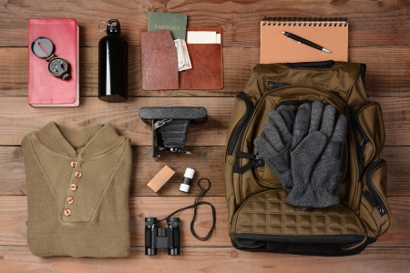 Photo pour Overhead view of gear laid out for a backpacking trip on a rustic wood floor. Items include, Backpack, gloves, sweater, camera, film, binoculars, passport, wallet, canteen, compass, money,  - image libre de droit