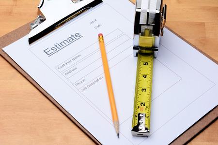 Photo pour Closeup of a Contractors estimate form with a pencil and tape measure on a wooden table - image libre de droit