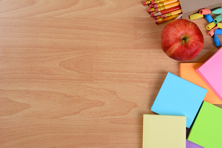 Photo pour High angle back to school still life on top of a wood teachers desk. An apple, note pads, pencils and erasers with copy space. - image libre de droit