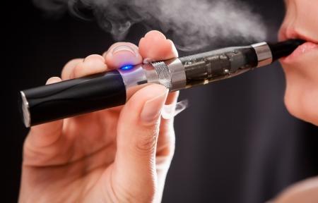 Photo pour Close up of a woman inhaling from an electronic cigarette  - image libre de droit