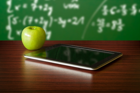 Photo pour Digital tablet and apple on the desk in front of blackboard - image libre de droit