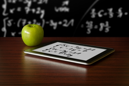 Foto de Digital tablet and apple on the desk in front of blackboard - Imagen libre de derechos