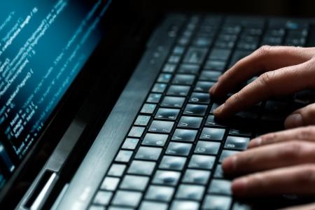 Foto de Hacker using laptop  Lots of digits on the computer screen  - Imagen libre de derechos