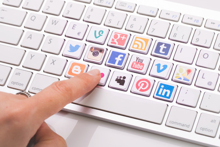 Photo pour BELCHATOW, POLAND - AUGUST 31, 2014: Male hand pointing on key with a social media logotype collection printed and placed on modern computer keyboard. - image libre de droit