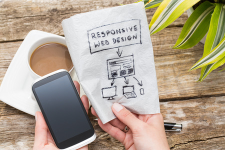 Foto de Web designer holding a blueprint of a new mobile application. Responsive web design concept. - Imagen libre de derechos