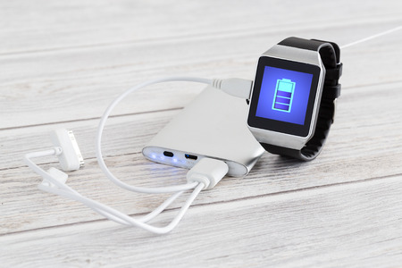 Foto per Smart watch charging with energy bank. Smartwatch concept. - Immagine Royalty Free