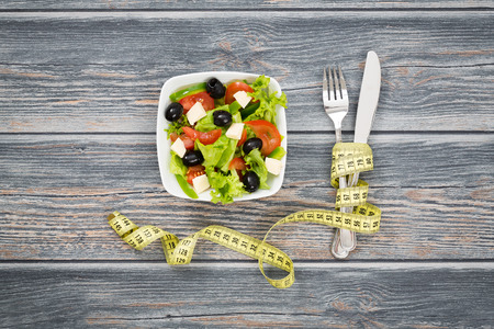 Photo pour Fitness salad and measuring tape on rustic wooden table. - image libre de droit