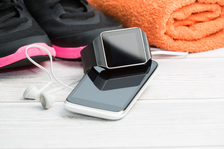 Foto per Fitness equipment, smart watch and phone on wood background. - Immagine Royalty Free