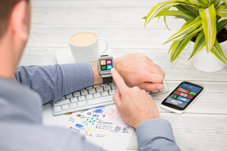 Photo for Businessman uses smart watch and phone. Smartwatch concept. - Royalty Free Image