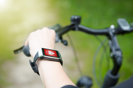 Foto de Woman riding a bike with a SmartWatch heart rate monitor. Smart watch concept. - Imagen libre de derechos