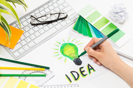 Photo pour Designer drawing a green light bulb. Brainstorming and inspiration cocnept. - image libre de droit