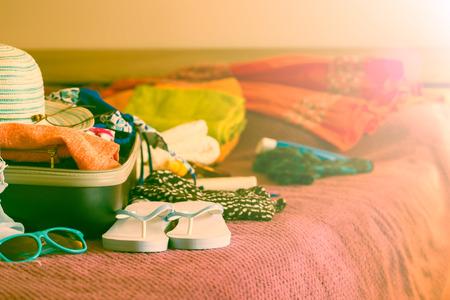 Foto de Open suitcase with clothing in the bedroom. Summer holiday concept. - Imagen libre de derechos