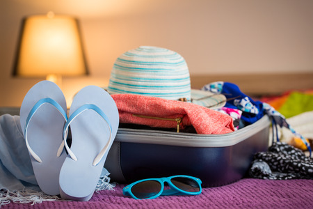 Foto de Open suitcase with clothing in the bedroom. Summer holiday concept. - Imagen libre de derechos