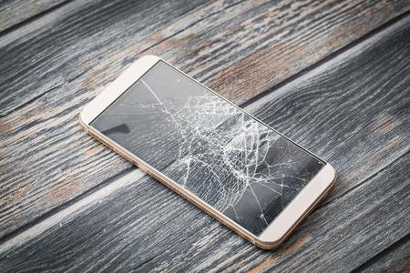 Foto de Modern broken mobile phone on wooden background. - Imagen libre de derechos