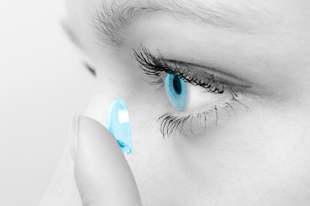 Photo for Woman inserting a contact lens in her eye. - Royalty Free Image