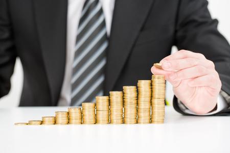 Foto de Saving money concept. Businessman hand putting money coin stack growing business. - Imagen libre de derechos