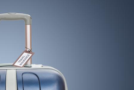 Photo pour Suitcase with travel insurance label on blue background. - image libre de droit