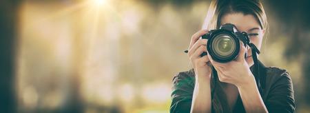 Foto de Portrait of a photographer covering her face with the camera. - Imagen libre de derechos