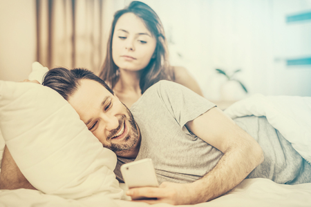Foto de A young couple lying in bed. One of them use the phone and flirting. The other person is jealous and spies of the arm. The concept of jealousy and distrust. - Imagen libre de derechos