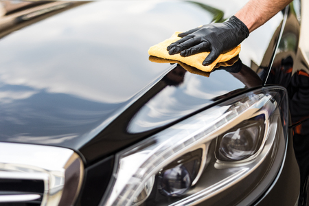 Photo for Car detailing - the man holds the microfiber in hand and polishes the car. Selective focus. - Royalty Free Image