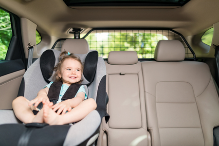 Foto de Beautyful smiling baby girl fastened with security belt in safety car seat - Imagen libre de derechos