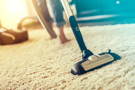 Photo for Young woman using a vacuum cleaner while cleaning carpet in the house. - Royalty Free Image