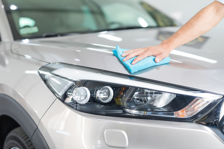 Photo pour Car detailing - the man holds the microfiber in hand and polishes the car. Selective focus. - image libre de droit