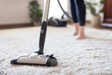 Photo pour Young woman using a vacuum cleaner while cleaning carpet in the house. - image libre de droit